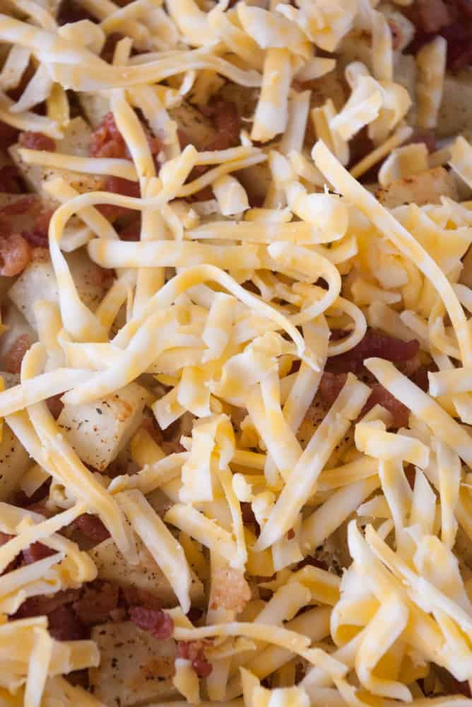 Bacon topped roasted potatoes sprinkled with grated cheese.
