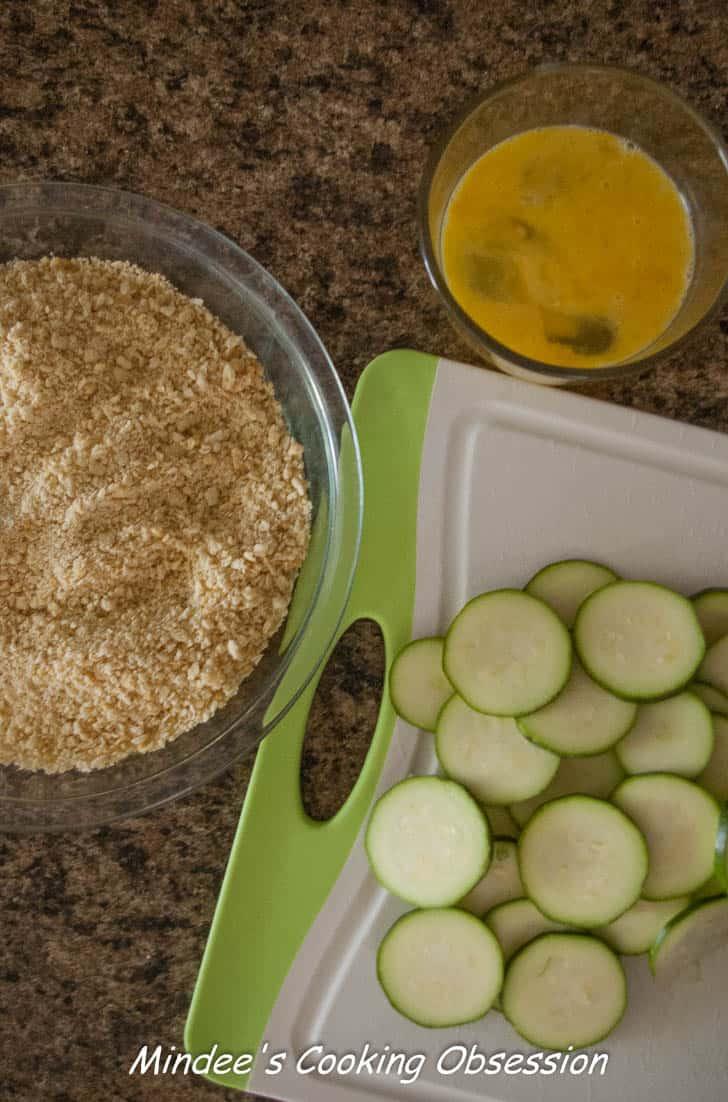 Zucchini slices, beaten eggs and saltine cracker crumbs ready to make crispy fried zucchini.