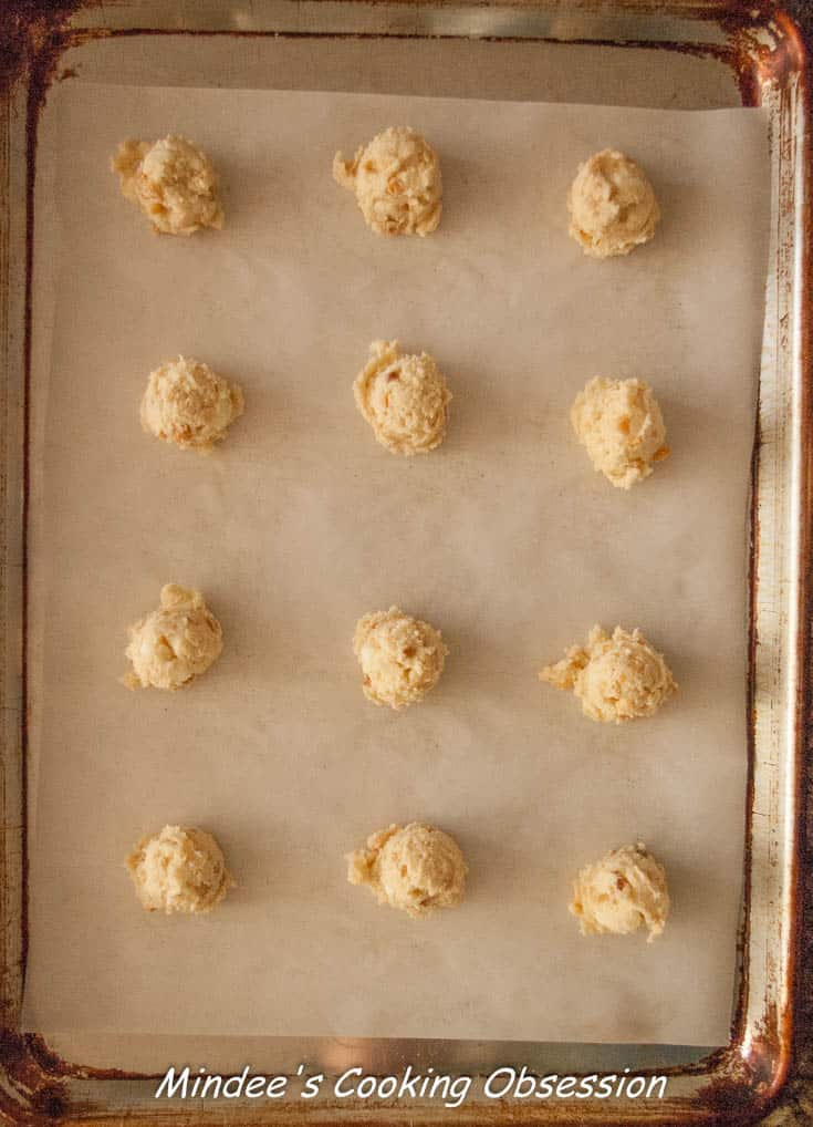 White Chocolate Chip Macadamia Nut Cookies scooped out onto a baking sheet.