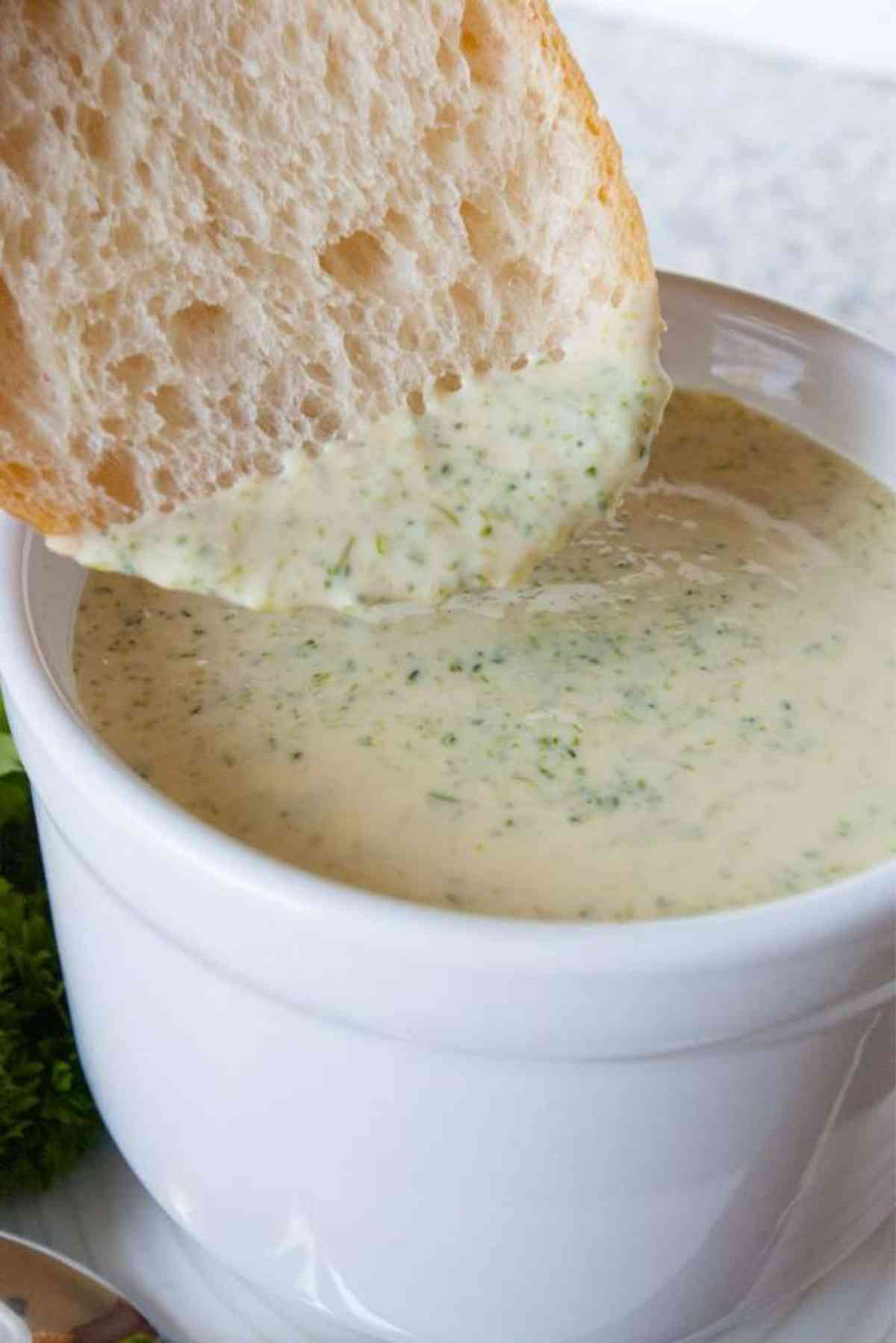 Slice of french bread being dipped into broccoli cheese soup.