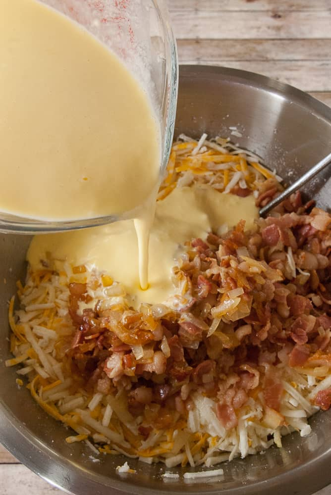 Egg mixture being poured over the hashbrowns, bacon and cheese.