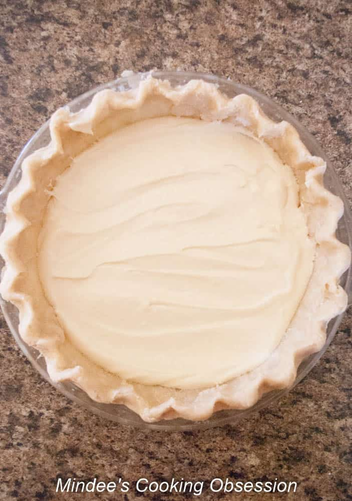 Apple Cheesecake Pie filling spread into the bottom of an unbaked pie shell.