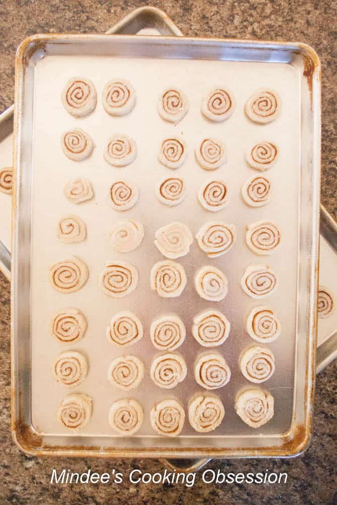 Pie Dough Cinnamon Swirl roll sliced and slices placed on a baking sheet.