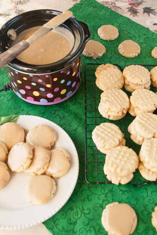 Butter cookies being frosted with caramel frosting.