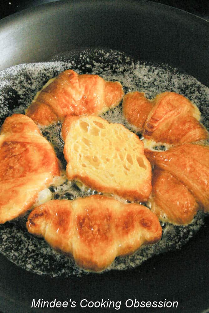 Dipped croissant being cooked in a frying pan.