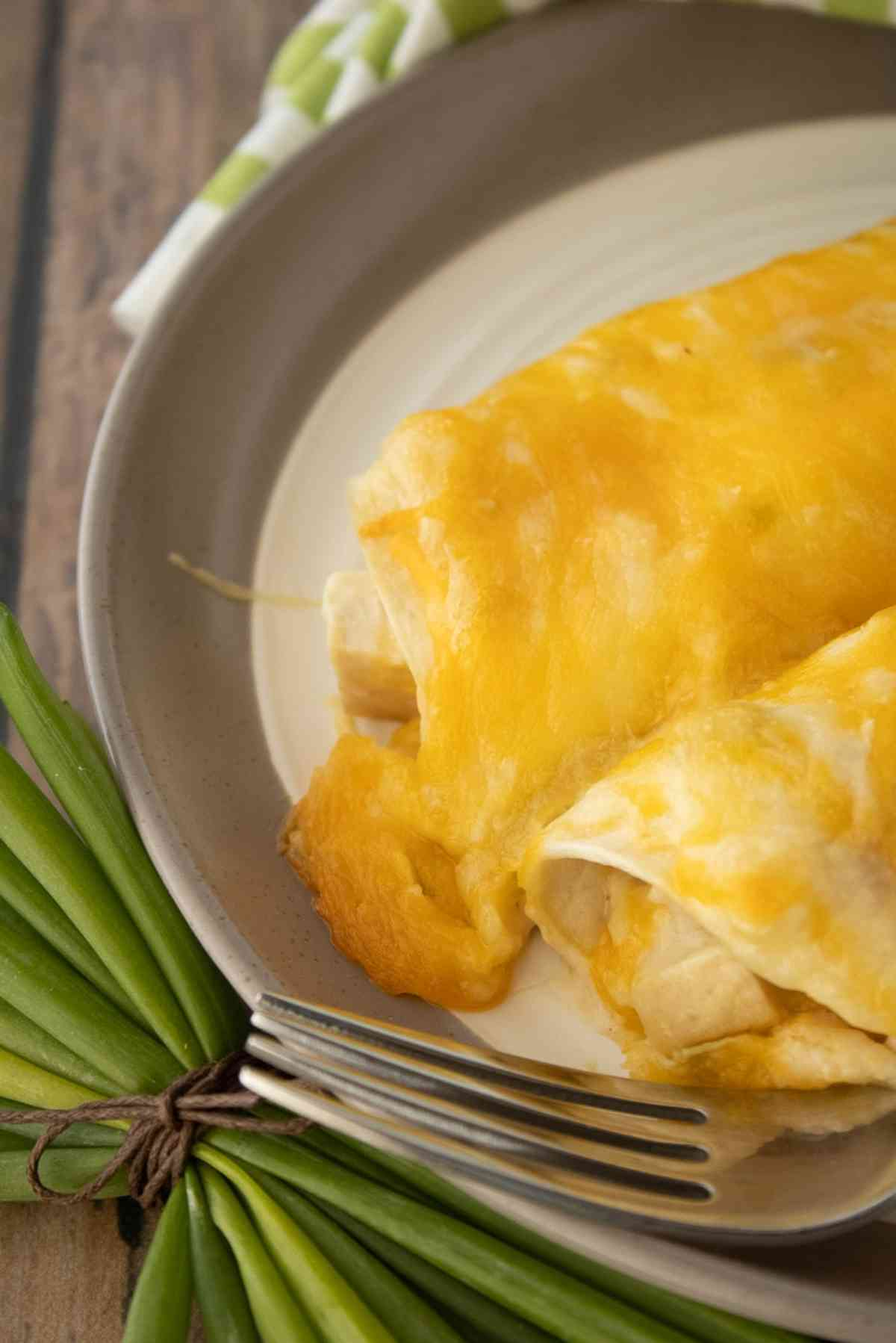 Two of the best ever chicken cheese enchiladas garnished with green onions.