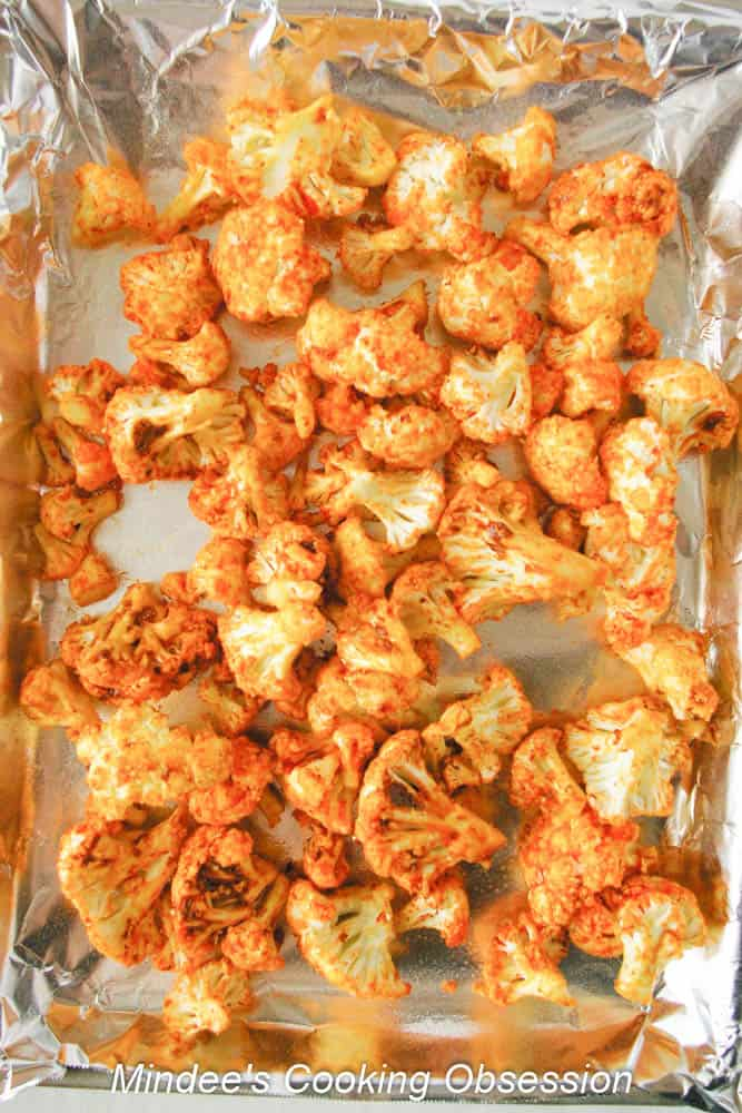 Seasoned cauliflower scattered across a baking sheet.
