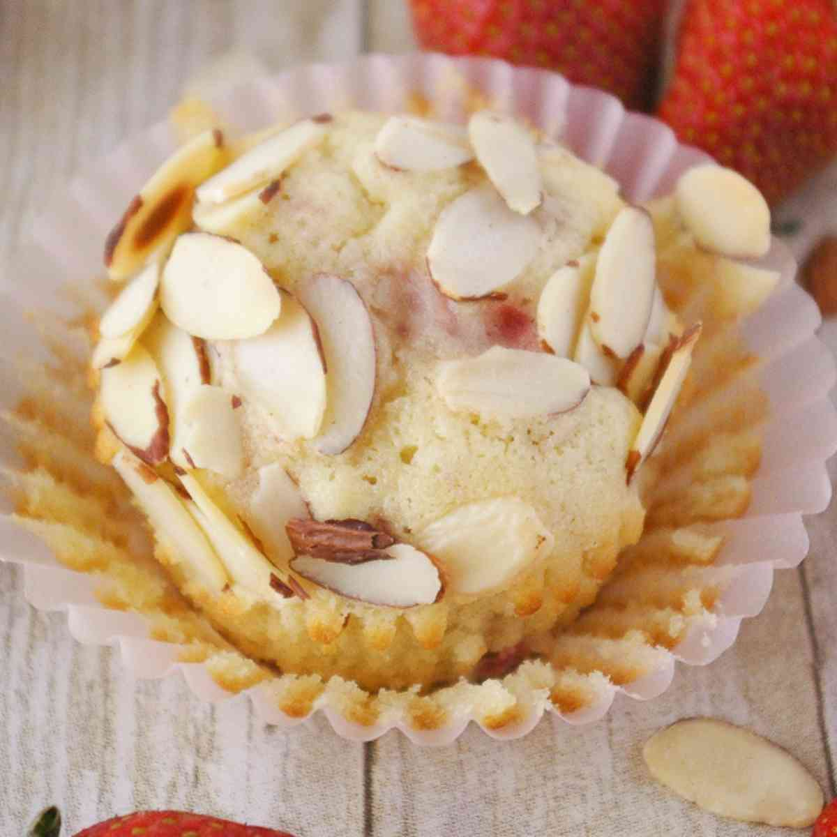 A strawberry almond muffin with the paper liner peeled off.