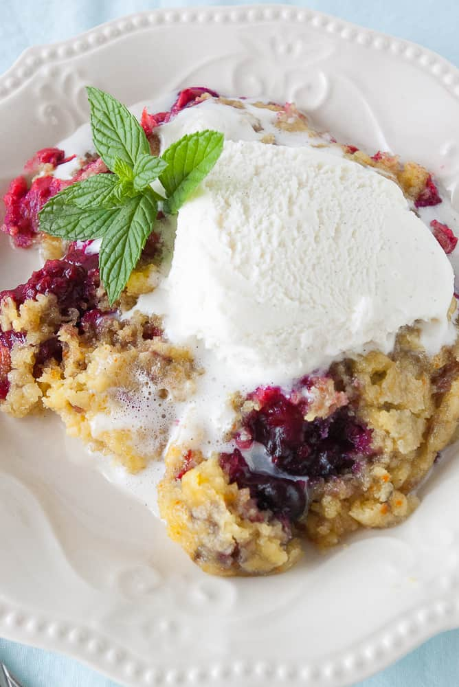 Slow Cooker triple berry cobbler topped with ice cream.