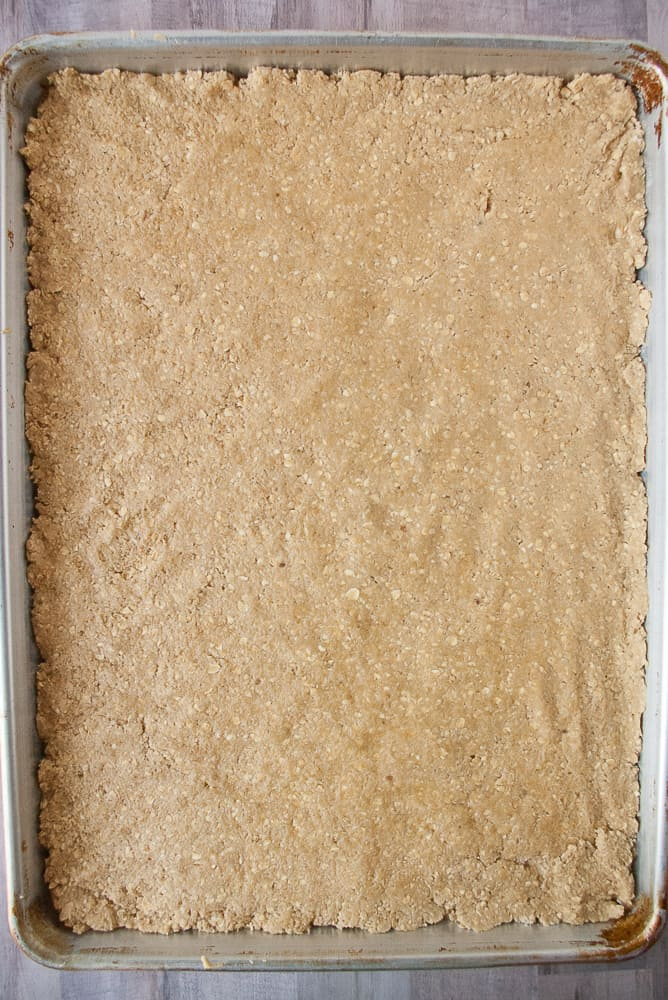 Oatmeal dough patted down into a baking sheet.