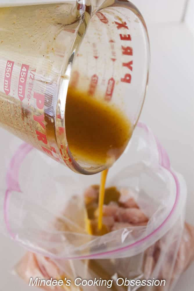 Marinade being poured over raw chicken bites in a ziploc bag.