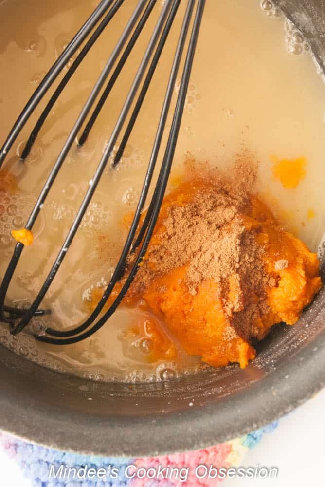 Pumpkin puree and spices being whisked into the syrup.