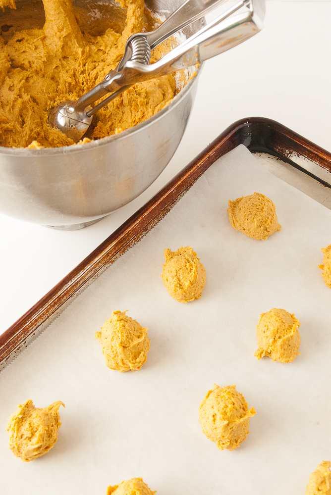 Pumpkin cookie dough scooped on a baking sheet.