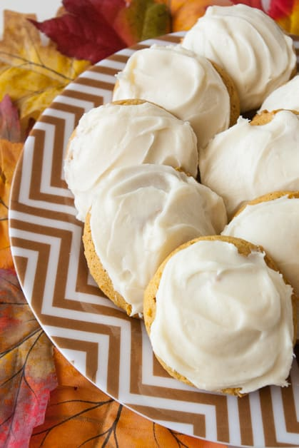 A plate of cream cheese frosted pumpkin cookies
