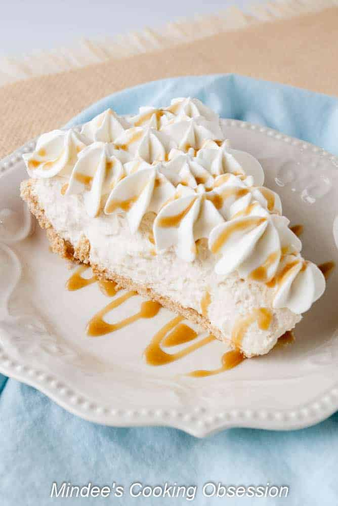 Caramel Cream Pie slice topped with whipped cream and drizzled with caramel.