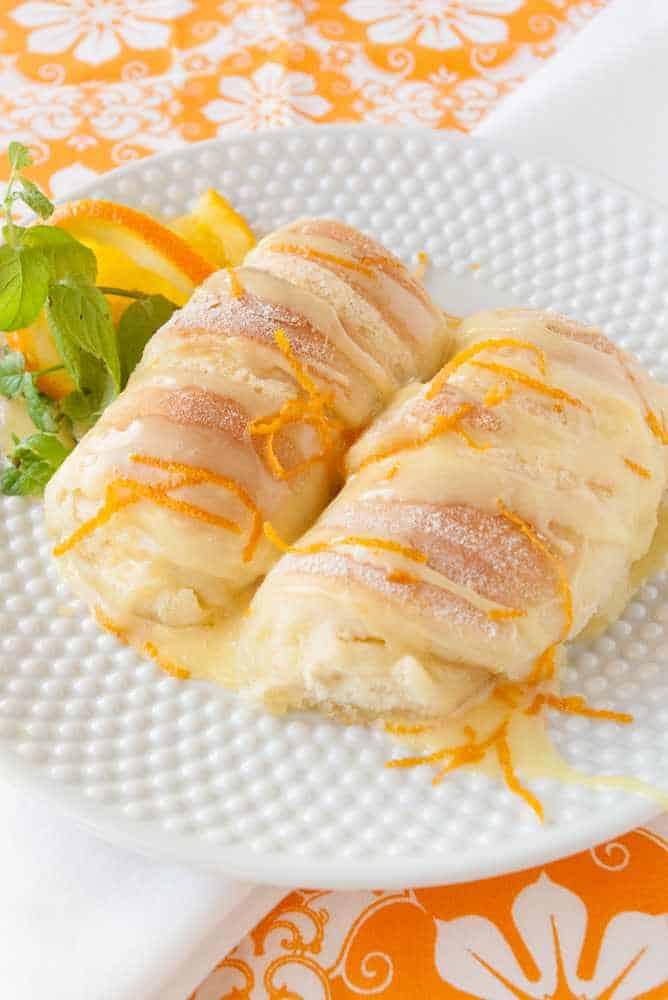 Two orange rolls on a plate.