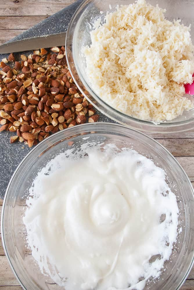 Chopped almonds, coconut mixture and stiffly beaten egg whites in bowls.