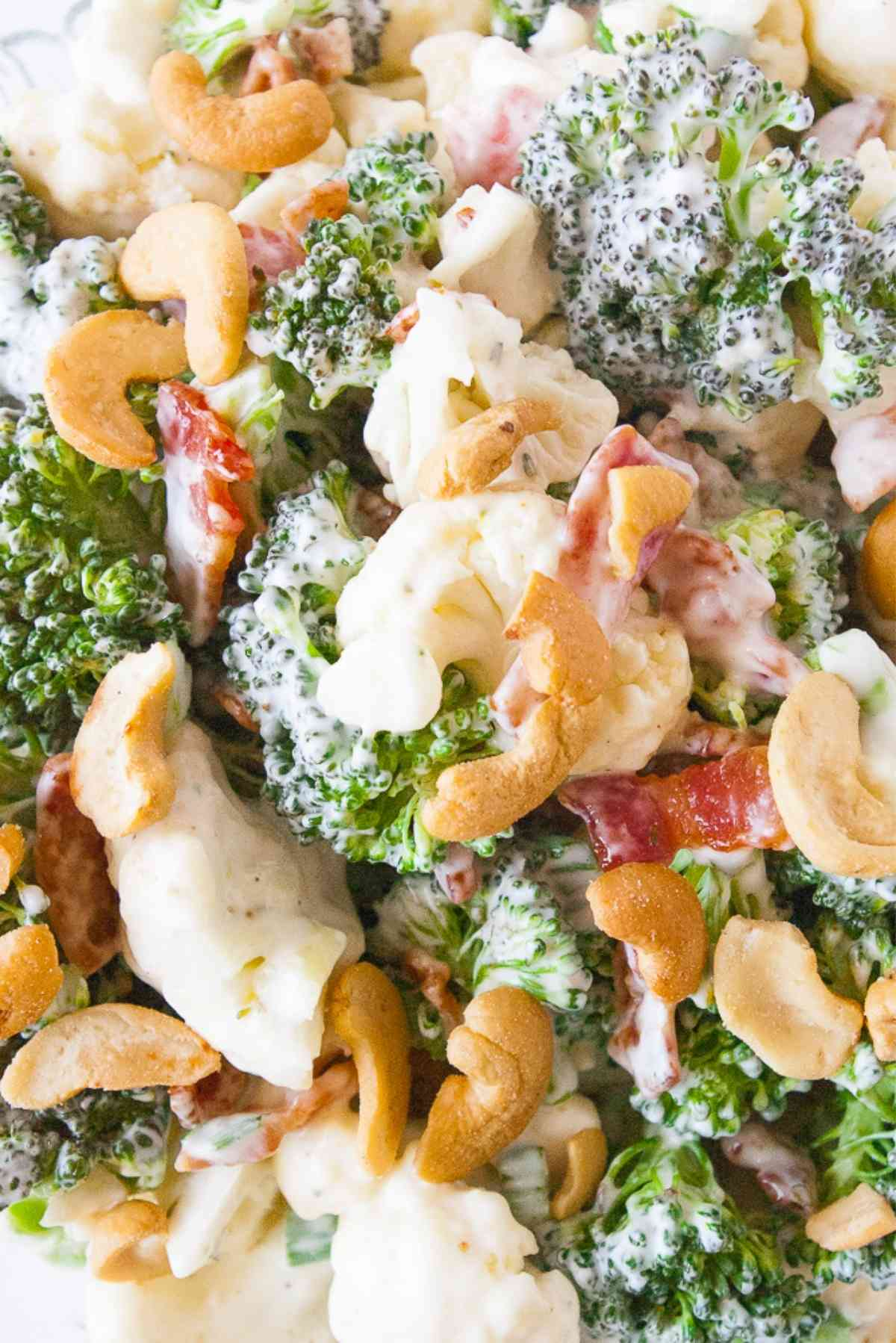 Close up of the broccoli, cauliflower, bacon and cashews in this salad.