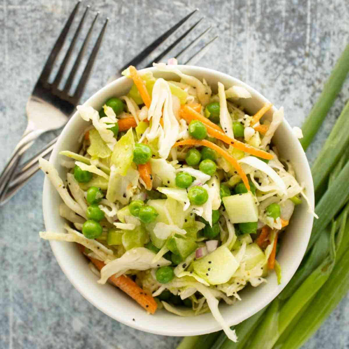 Bowl of poppy seed coleslaw garnished with green onions.