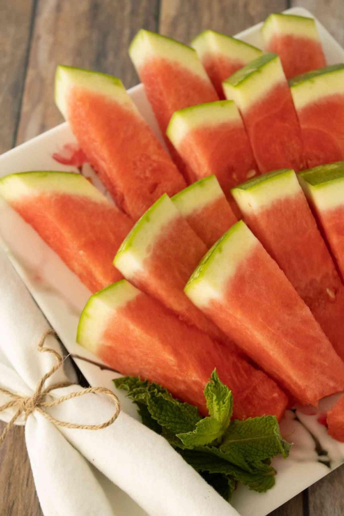 Melon sticks arranged on a platter garnished with fresh mint leaves.