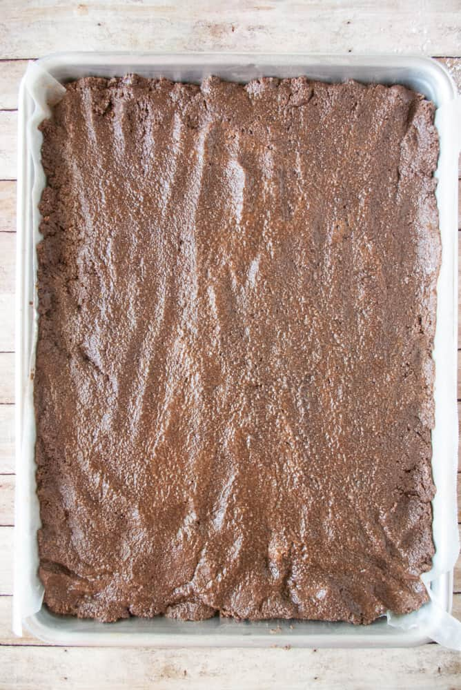 Chocolate peanut butter filling pressed into a pan.