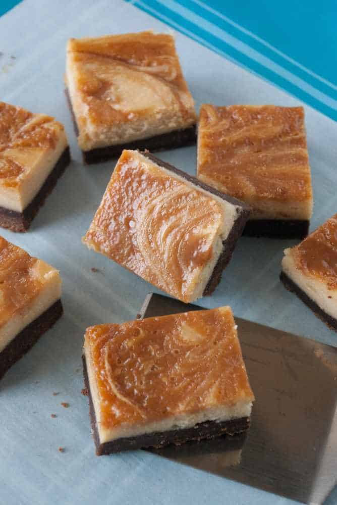 Squares of caramel swirl cheesecake brownies.