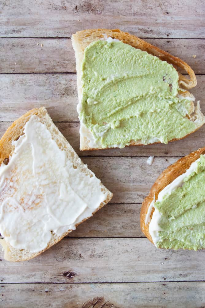 Sourdough halves spread with mayo and guacamole.