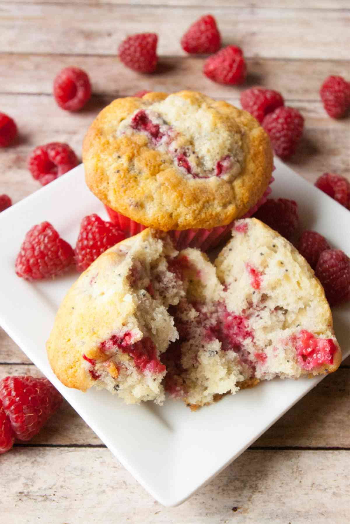 Warm raspberry muffins on a plate surrounded by fresh raspberries.