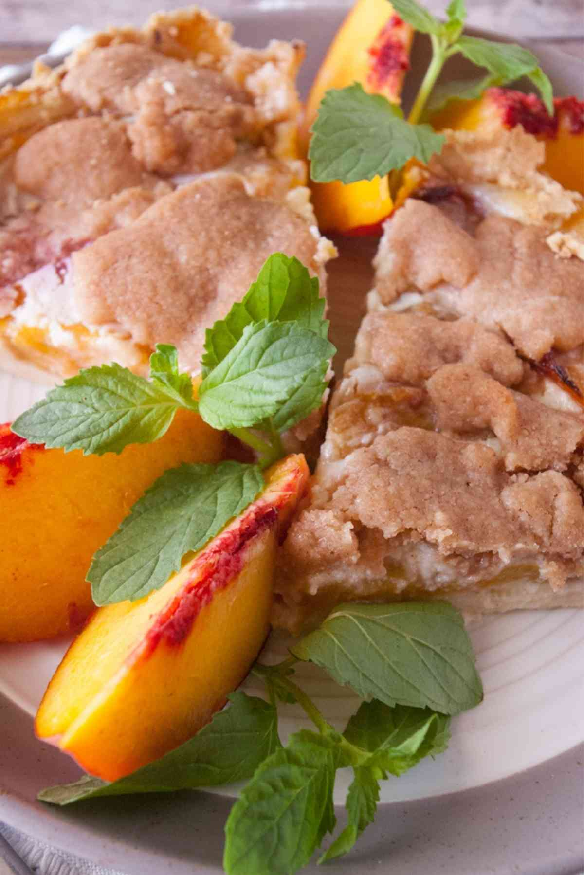 Slices of fresh peach pie topped with a streusel crumb topping garnished with fresh peaches and mint.