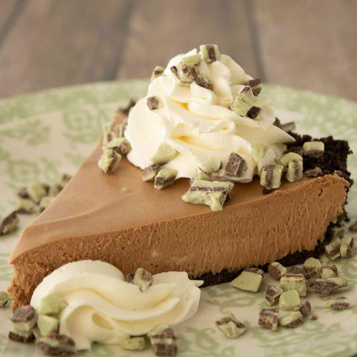 Slice of grasshopper pie garnished with whipped cream.