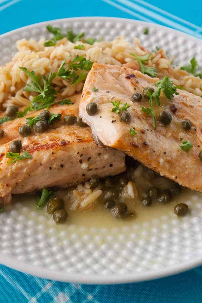 Salmon piccata plated on a bed of rice.