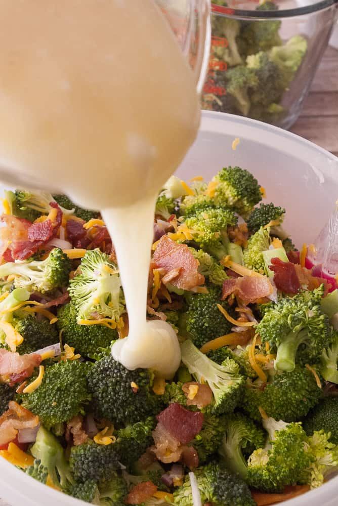 Dressing being poured over the broccoli salad.