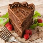 Big slice of chocolate cake by two forks.