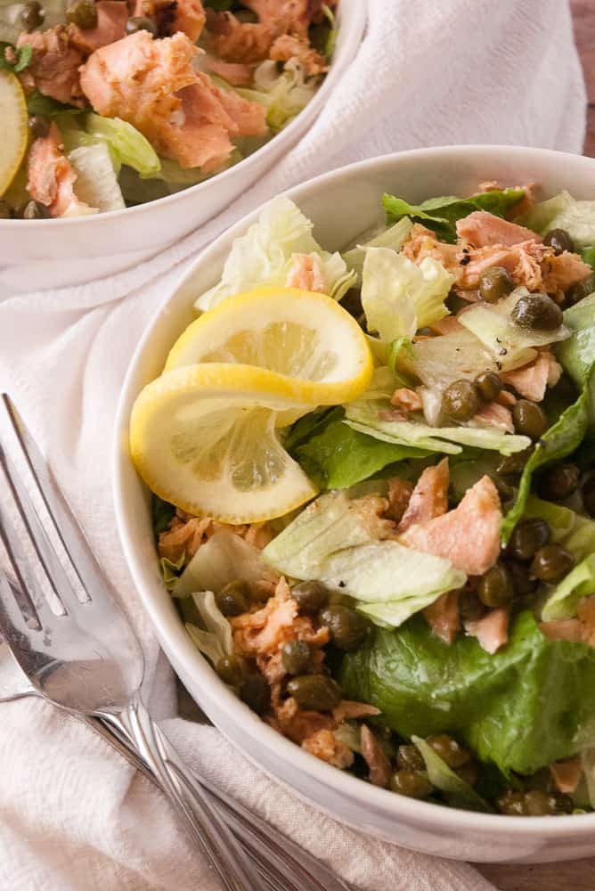 Salmon Piccata Salad in dinner bowls garnished with lemon slices.