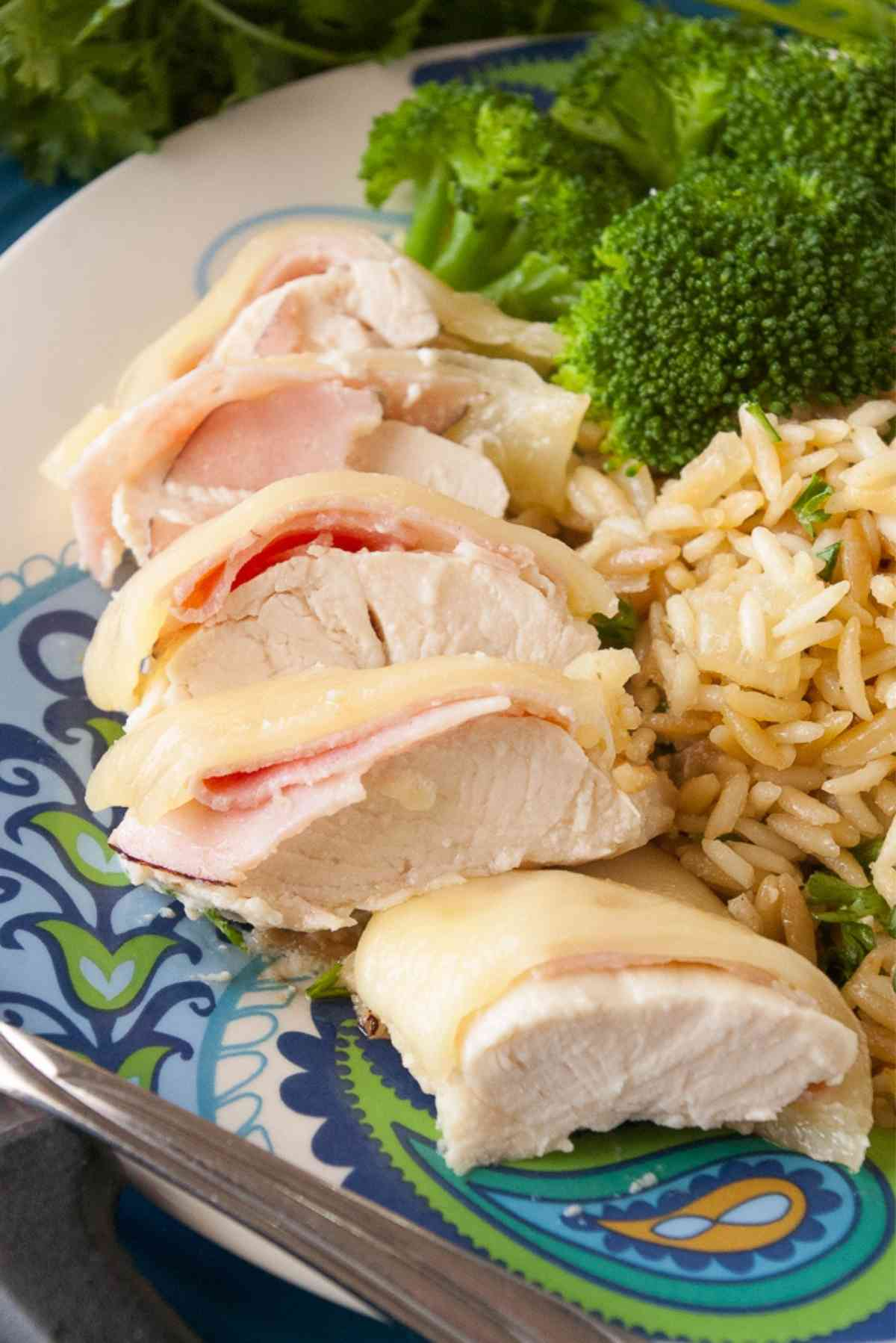 A plate with chicken cordon bleu, broccoli and rice.