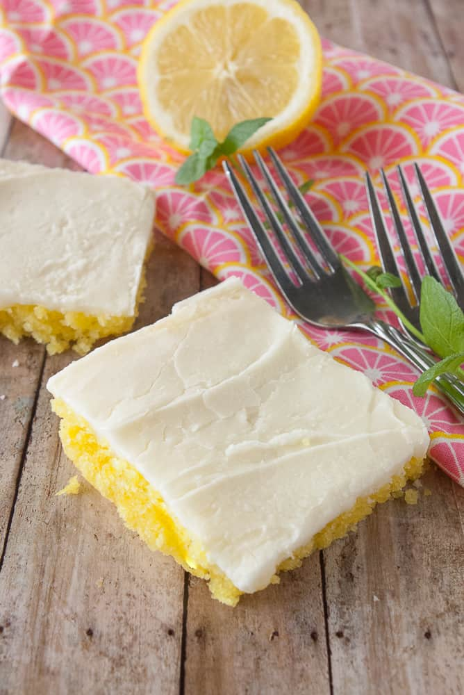 A piece of lemon sheet cake with forks.