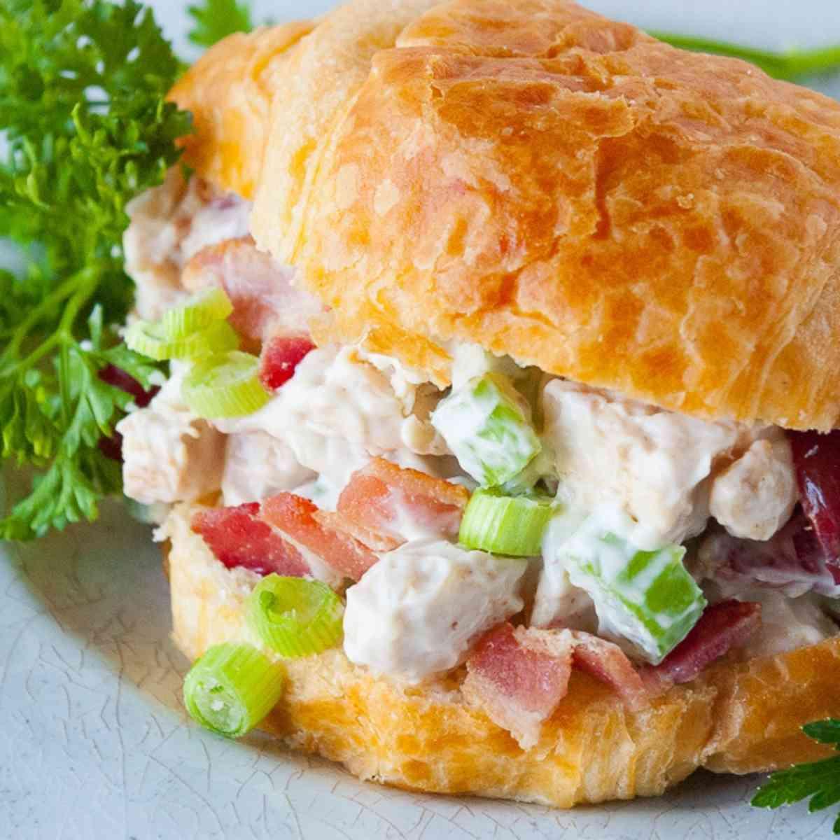Chicken salad croissant sandwich garnished with parsley.