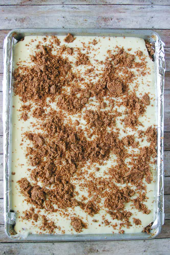Chocolate crumbles being sprinkled over the filling for the cheesecake bars.