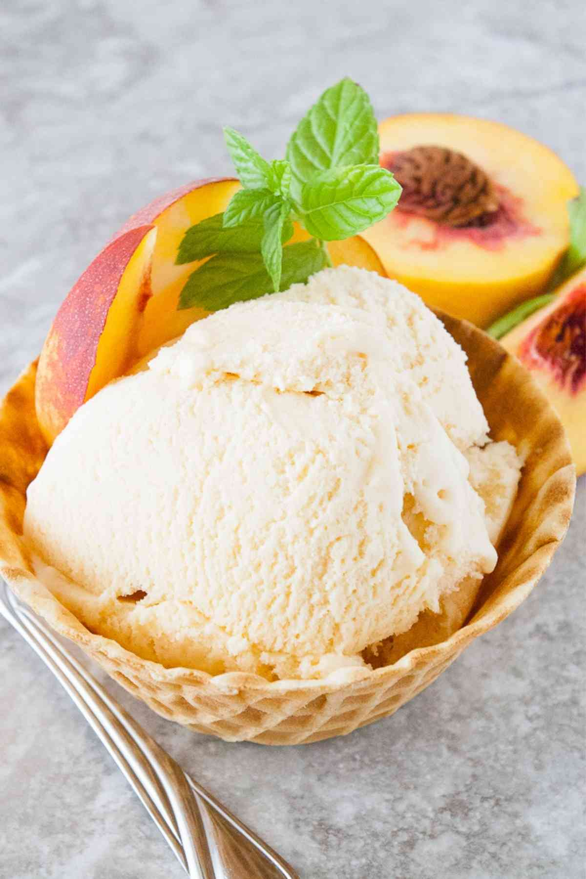 Waffle bowl of homemade peach ice cream garnished with fresh peaches and mint.