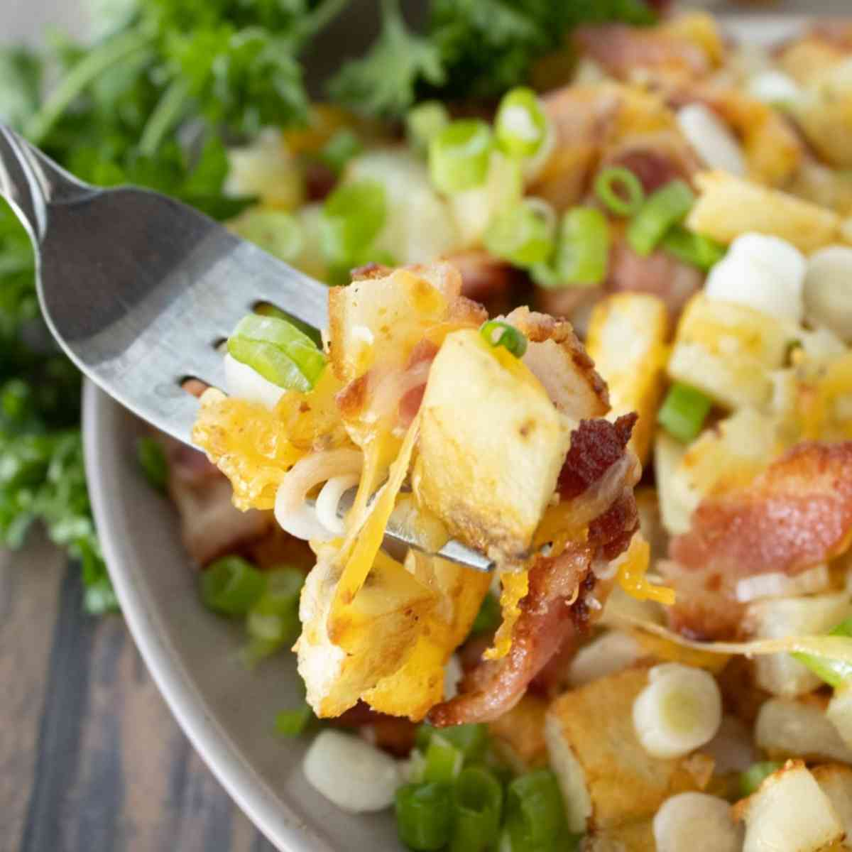 Forkful of crispy potatoes covered in bacon and cheese.
