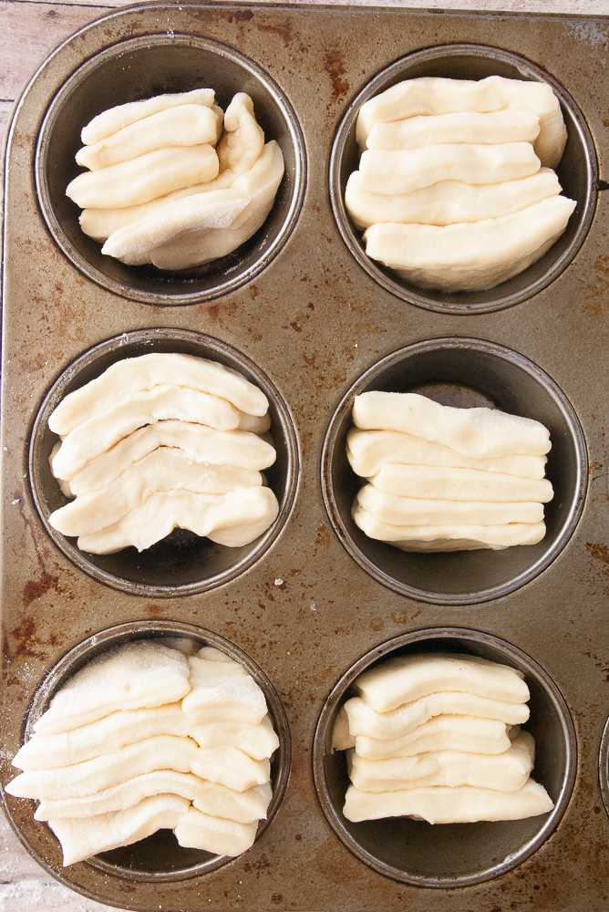Unbaked butterflake rolls in a muffin tins.