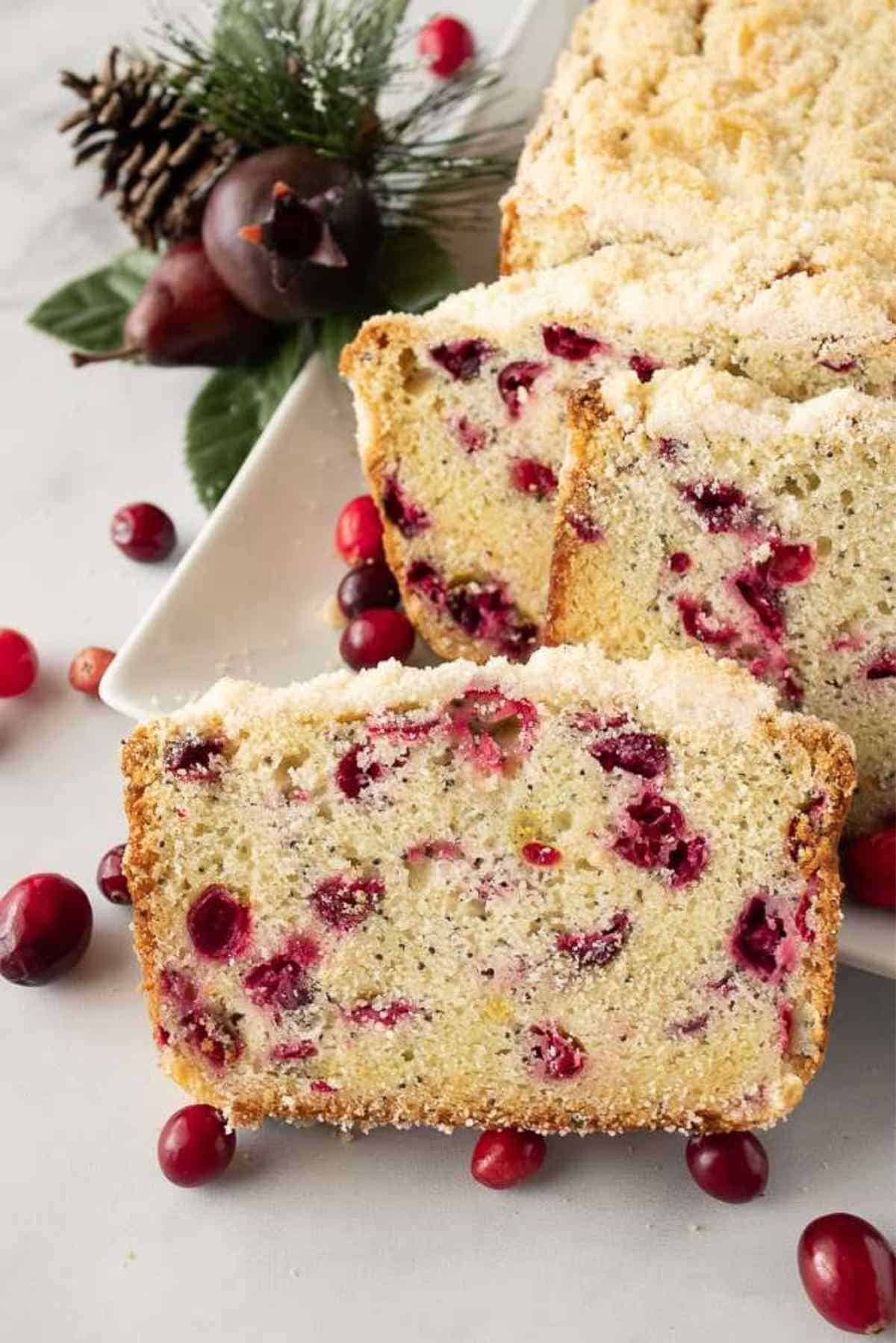 A finished loaf of cranberry poppy seed bread placed and sliced on a long plate garnished with fresh cranberries.