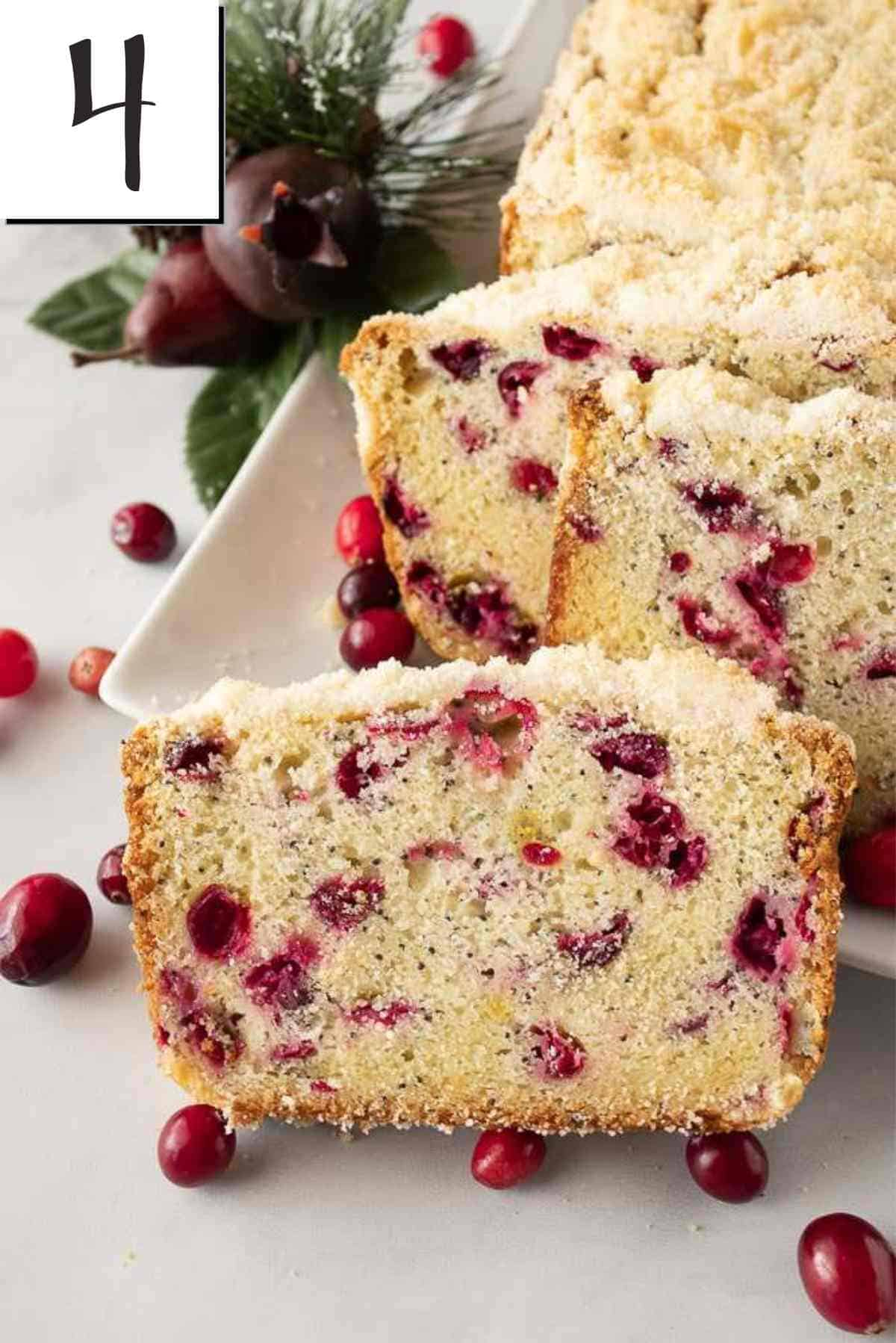 A baked loaf of cranberry poppy seed bread on a decorative plate garnished with fresh cranberries