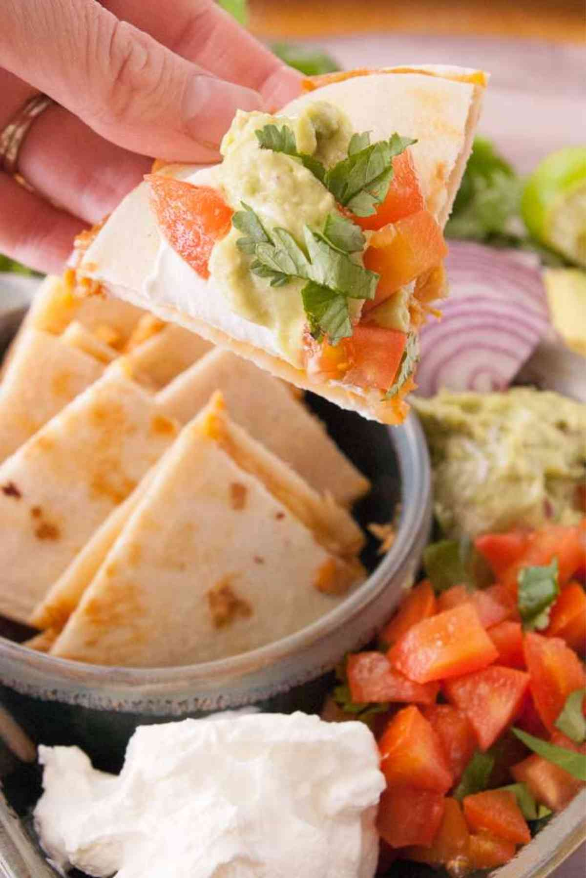 Buffalo Chicken Quesadillas topped with guac, sour cream, lettuce and tomatoes.