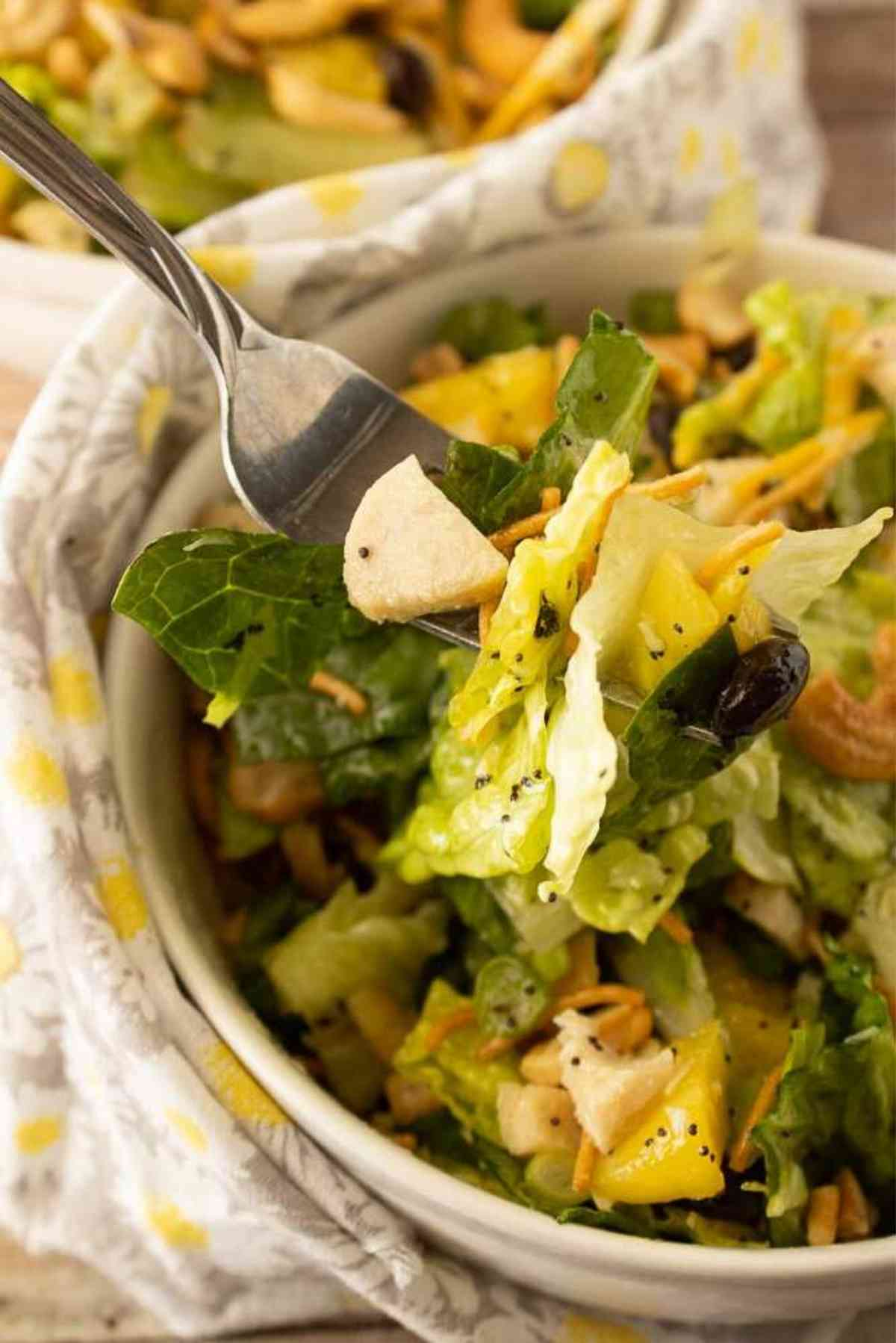 A fork lifting a bite of lettuce, chicken, black beans and pineapple coated with poppy seed dressing.