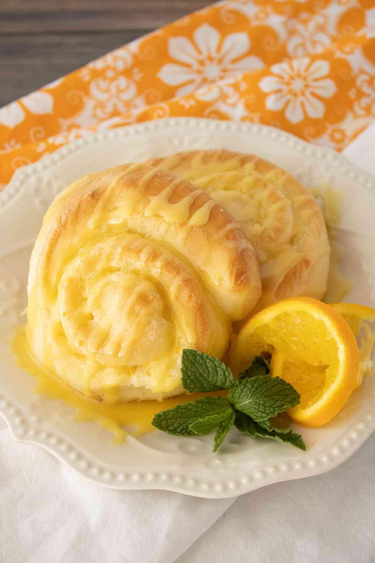 Orange rolls garnished with orange slice and mint leaves.