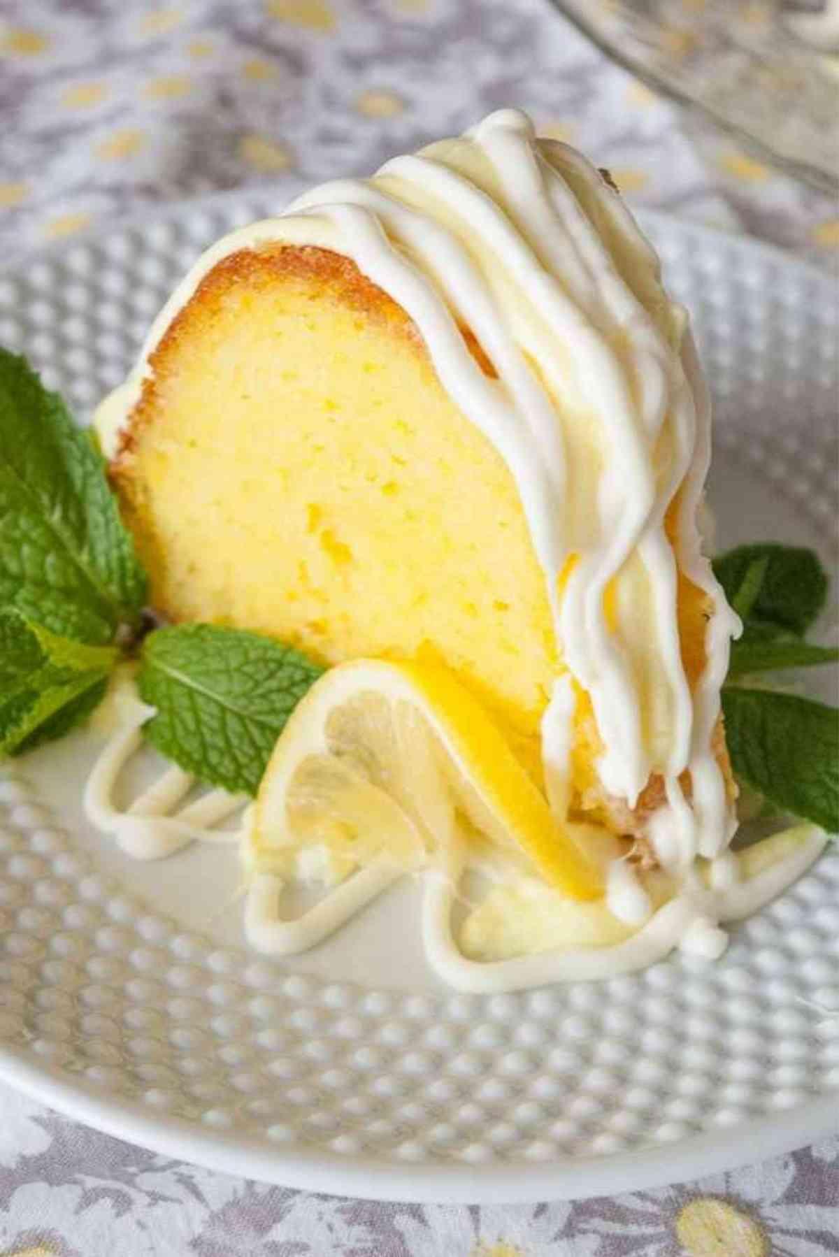 Slice of lemon bundt cake iced and garnished with mint leaves.