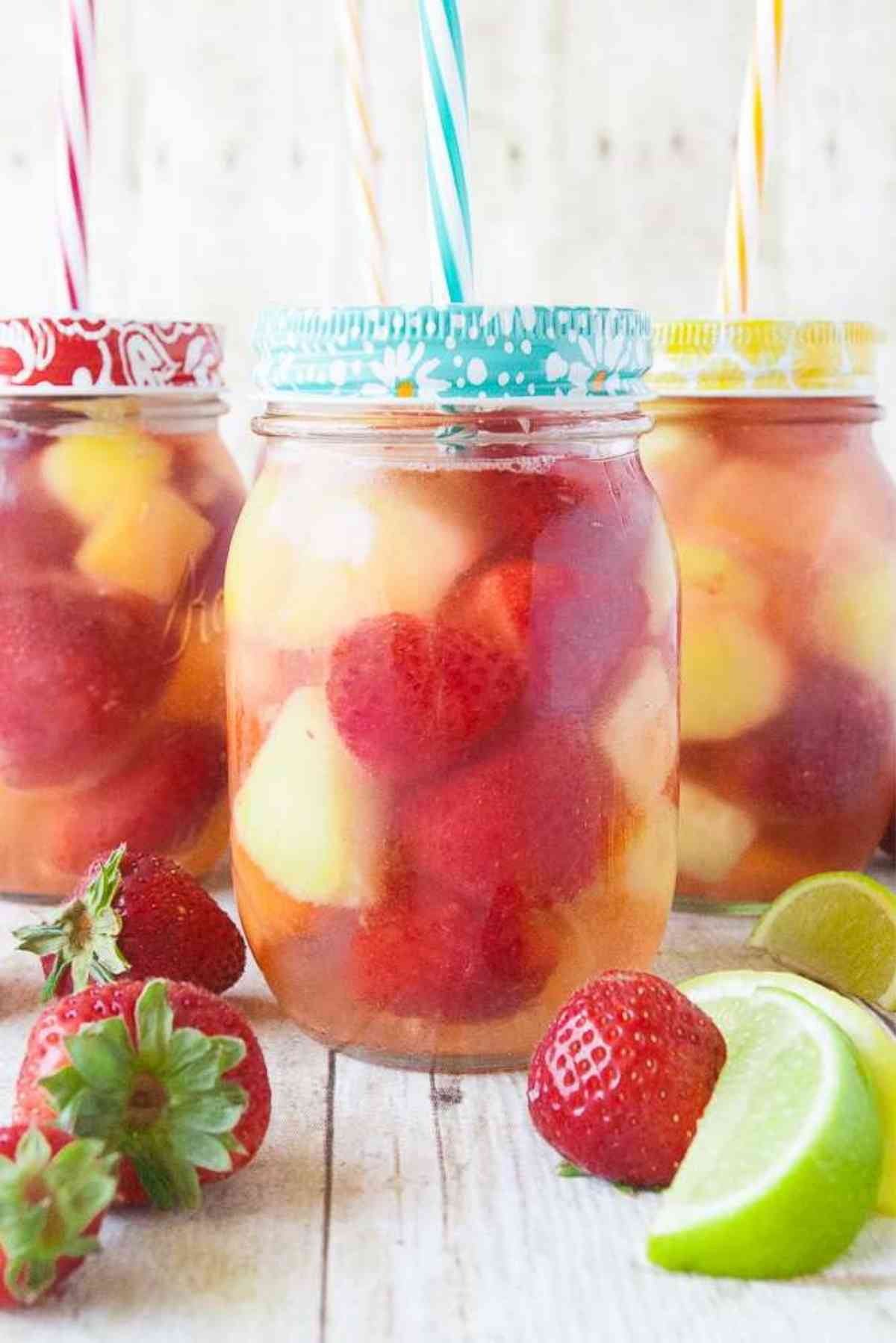 Decorative mason jars filled with mixed fruit punch.