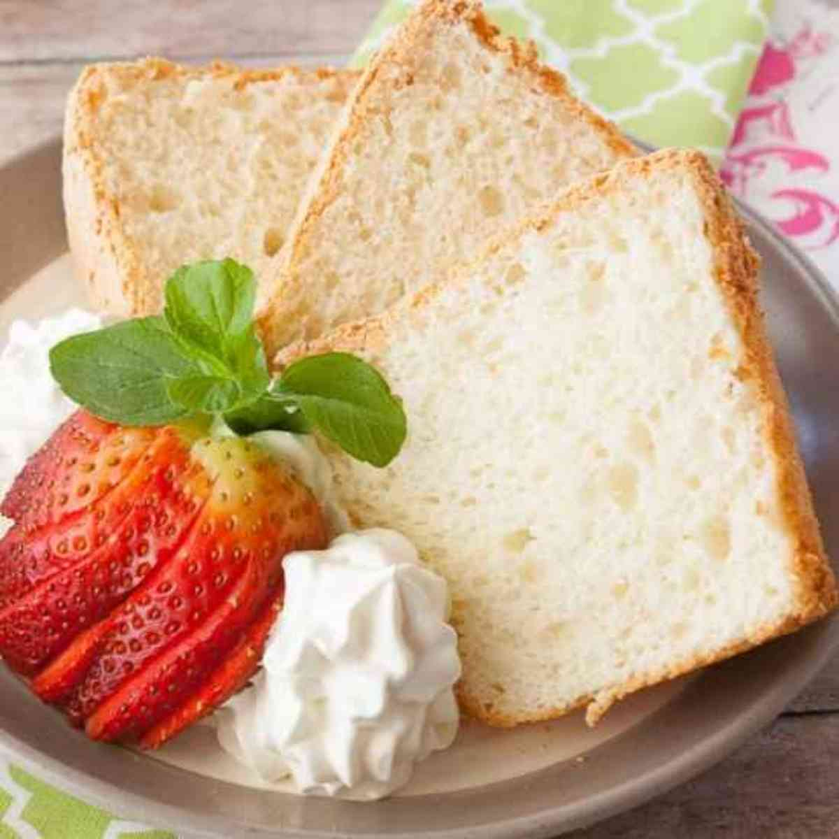 Three slices of angel food cake with fresh strawberries.