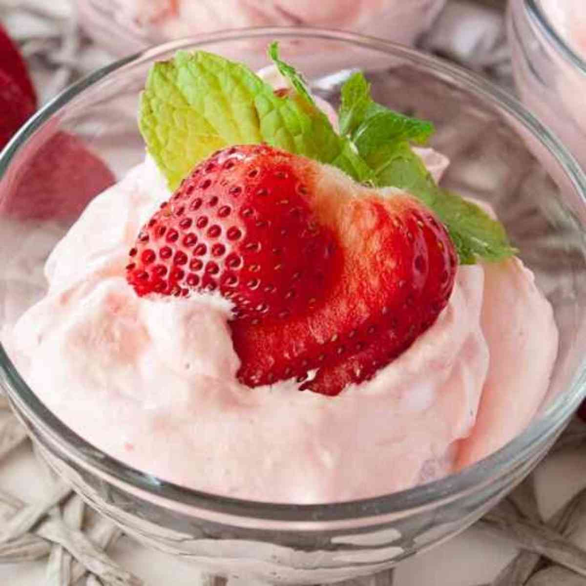 Bowl of berries and cream jello salad garnished with a strawberry.